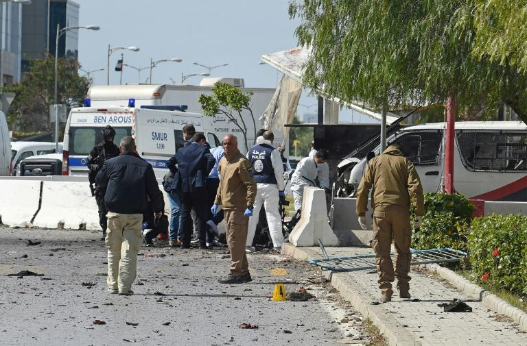 Police and forensic experts inspect the scene of a twin attack near the US embassy in Tunis
