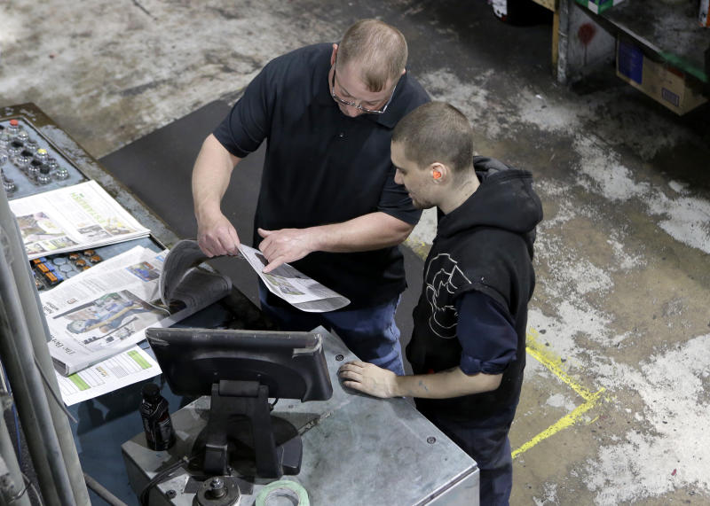 In this Thursday, April 11, 2019 photo pressmen Kit Stover, of Richmond, Mass., left, and Lukus Ladeinde, of Pittsfield, Mass., right, check for correct registration of print from a sample of a newspaper fresh off the press at The Berkshire Eagle newspaper, in Pittsfield, Mass. The paper now features a new 12-page lifestyle section for Sunday editions, a reconstituted editorial board, a new monthly magazine, and the newspaper print edition is wider. That level of expansion is stunning in an era where U.S. newspaper newsroom employment has shrunk by nearly half over the past 15 years. (AP Photo/Steven Senne)