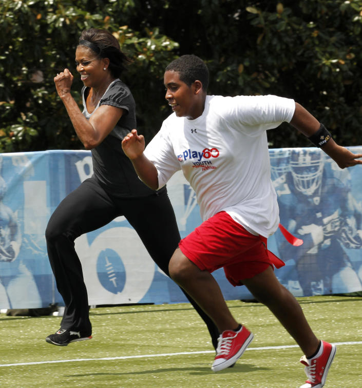 """FILE - In this Sept. 8, 2010, file photo, first lady Michelle Obama runs a 40-yard sprint as she participates in the Let's Move! Campaign and the NFL's Play 60 Campaign festivities with area youth, to promote exercise and fight childhood obesity in New Orleans. Michelle Obama has a new look, both in person and online, and with the president's re-election, she has four more years as first lady, too. The first lady is trying to figure out what comes next for this self-described """"mom in chief"""" who also is a champion of healthier eating, an advocate for military families, a fitness buff and the best-selling author of a book about her White House garden. For certain, she'll press ahead with her well-publicized efforts to reduce childhood obesity and rally the country around its service members. (AP Photo/Gerald Herbert, file)"""