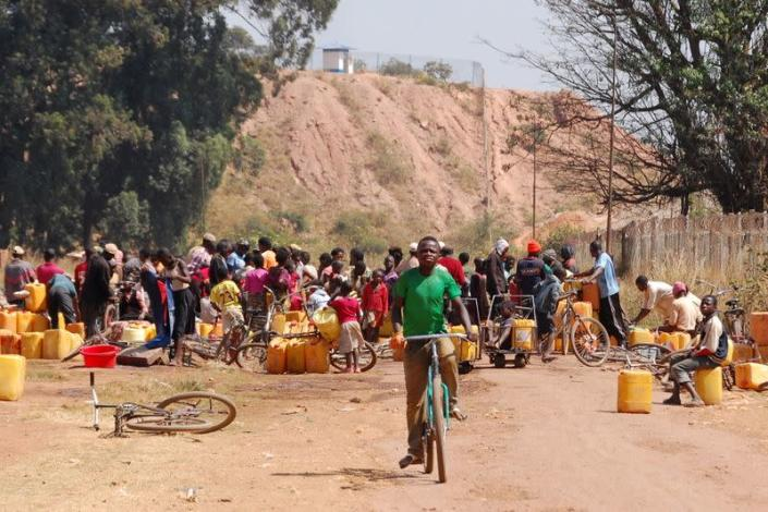 FILE PHOTO: People fetch water outside a copper and cobalt mine run by Sicomines in Kolwezi
