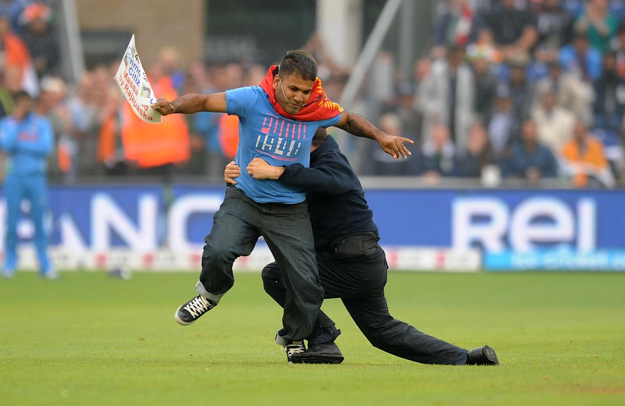 A protester is tackled after he runs onto the pitch during the ICC Champions Trophy, Semi Final at the SWALEC Stadium, Cardiff.