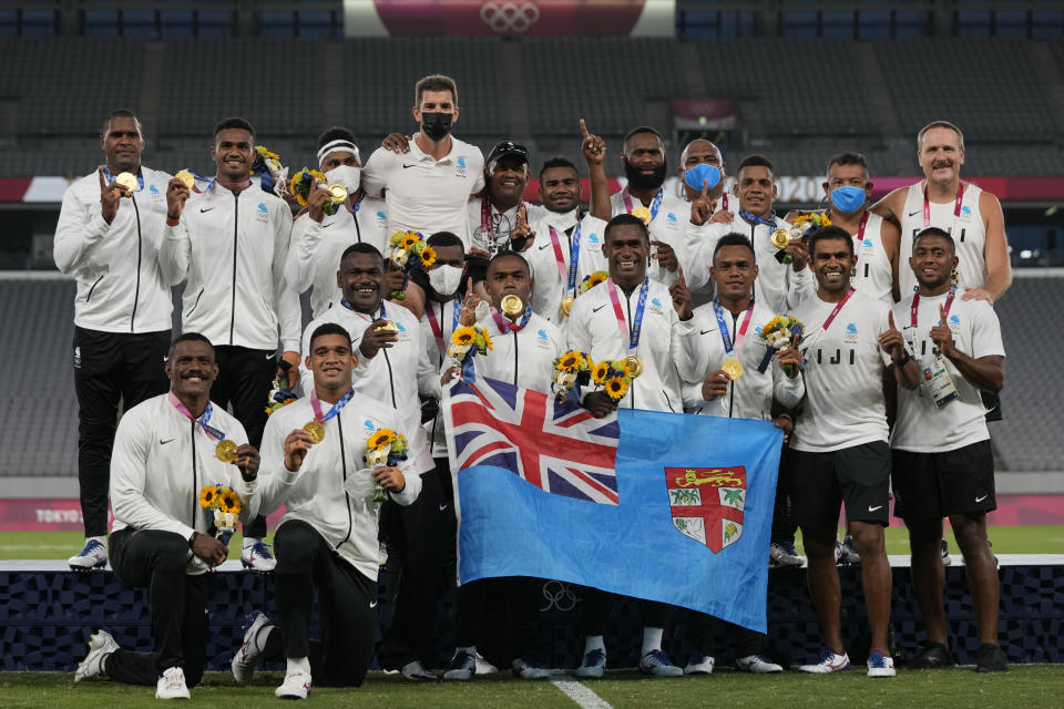 Fiji players and team staff poses with their gold medals and a national flag, after winning men's rugby sevens at the 2020 Summer Olympics, Wednesday, July 28, 2021 in Tokyo, Japan. (AP Photo/Shuji Kajiyama)