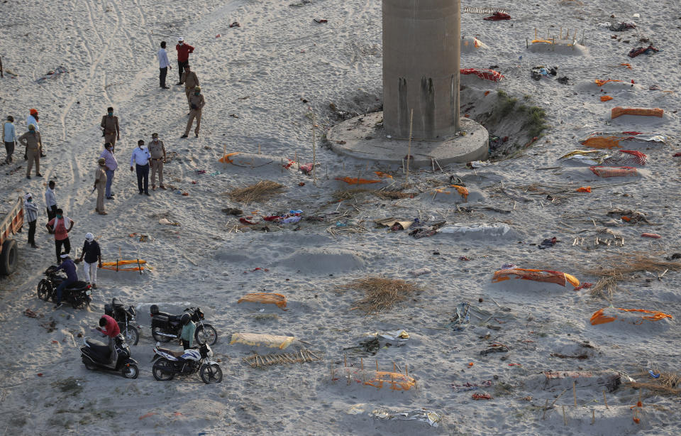 Bodies of suspected Covid-19 coronavirus victims are seen in shallow graves buried in the sand near a cremation ground on the banks of Ganges River.