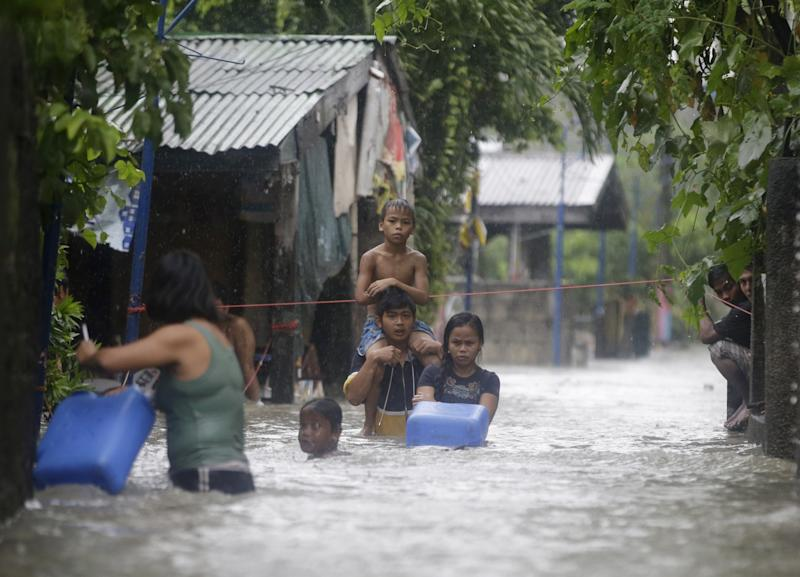 Residents wade through a flooded street in Binakayan township, Cavite province, south of Manila, Philippines Monday, Aug. 19, 2013. Torrential rains brought the Philippine capital to a standstill Monday, submerging some areas in waist-deep floodwaters and making streets impassable to vehicles while thousands of people across coastal and mountainous northern regions fled to emergency shelters. (AP Photo/Bullit Marquez)