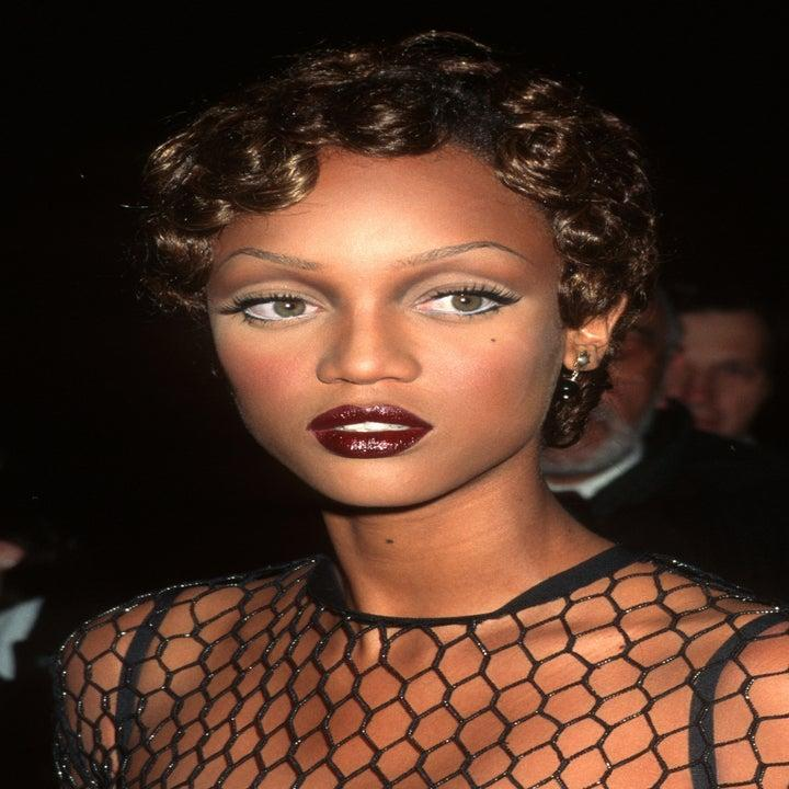 Tyra Banks wearing a deep red lip and a black net style top