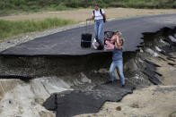 Tourists walk try to walk along a road damaged by flooding near the village of Tsybanobalka, Krasnodar region, Russia, Saturday, Aug. 14, 2021. Heavy rains have flooded broad areas in southern Russia, forcing the evacuation of more than 1,,500 people. Authorities in the Krasnodar region said Saturday that more than 1,400 houses have been flooded following storms and heavy rains that swept the area this week. (AP Photo)