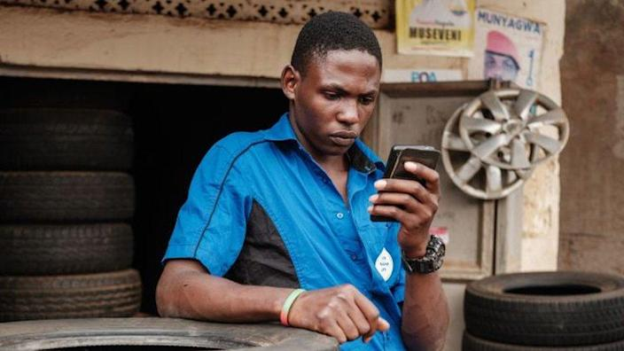 A man browses Facebook on his smart phone after the mobile internet went back online in Kampala