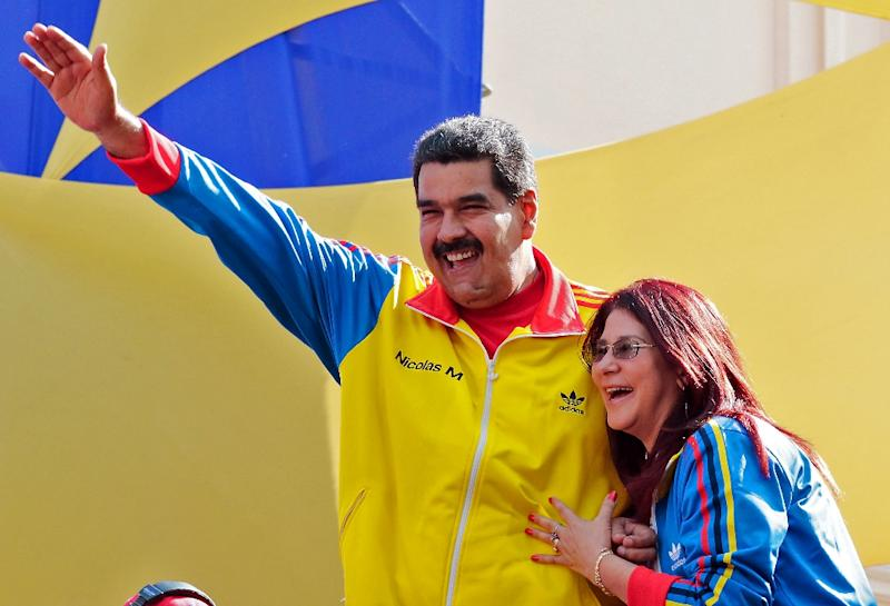 Handout photo released by the Venezuelan Presidency of President Nicolas Maduro (L) waving next to First Lady Cilia Flores (R) during a rally in Caracas on August 28, 2015