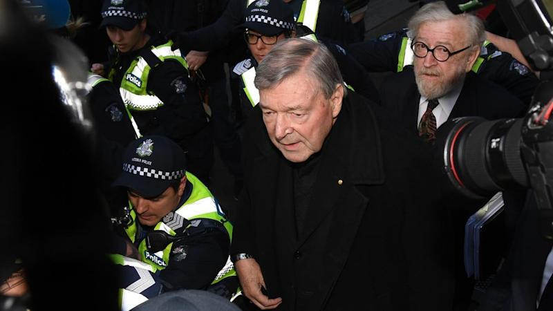 Cardinal George Pell arrives at a Melbourne court with a police escort.