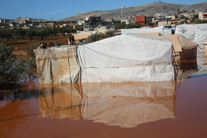 """<span class=""""caption"""">Refugee camps in Idlib, Syria, flooded in heavy rains, Jan. 31, 2021.</span> <span class=""""attribution""""><a class=""""link rapid-noclick-resp"""" href=""""https://www.gettyimages.com/detail/news-photo/heavy-rainstorm-flood-syrian-refugee-camps-in-idlib-syria-news-photo/1230888430?adppopup=true"""" rel=""""nofollow noopener"""" target=""""_blank"""" data-ylk=""""slk:Muhammad al-Rifai/NurPhoto via Getty Images"""">Muhammad al-Rifai/NurPhoto via Getty Images</a></span>"""