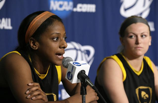 Iowa guard Theairra Taylor, left, speaks during a news conference for the NCAA women's college basketball tournament as teammate Melissa Dixon, right, sits near, Monday, March 24, 2014, in Iowa City, Iowa. Iowa plays Louisville in a second-round game on Tuesday. (AP Photo/Charlie Neibergall)