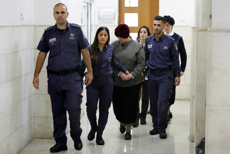 Malka Leifer (C), a former Australian teacher accused of dozens of cases of sexual abuse of girls at a school, is escorted by police as she arrives for a court hearing