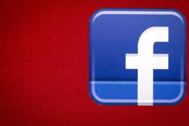 A Facebook logo is displayed on the side of a tour bus in New York's financial district