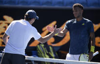 Russia's Aslan Karatsev, left, and Canada's Felix Auger-Aliassime shake hands after Karatsev won their fourth round match at the Australian Open tennis championships in Melbourne, Australia, Sunday, Feb. 14, 2021. The Australian Open continues but without crowds after the Victoria state government imposed a five-day lockdown in response to a COVID-19 outbreak at a quarantine hotel. (AP Photo/Andy Brownbill)