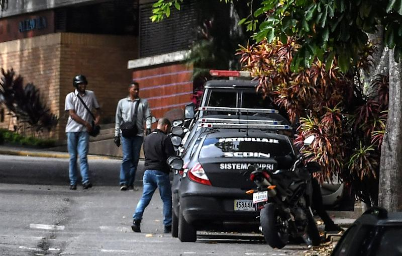 Venezuelan intelligence service members stand guard outside the home of ousted attorney general Luisa Ortega, who says it was raided and searched