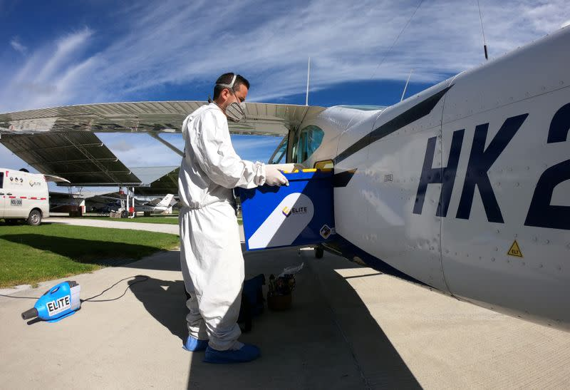 A man wearing protective gear disinfects a plane before takeoff of a flight that goes to villages with difficult access to collect samples of coronavirus disease (COVID-19), in Bogota