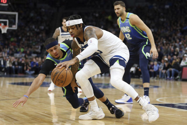 Minnesota Timberwolves' D'Angelo Russell handles the ball against Dallas Mavericks' Seth Curry in the first half of an NBA basketball game Sunday, March 1, 2020, in Minneapolis. (AP Photo/Stacy Bengs)