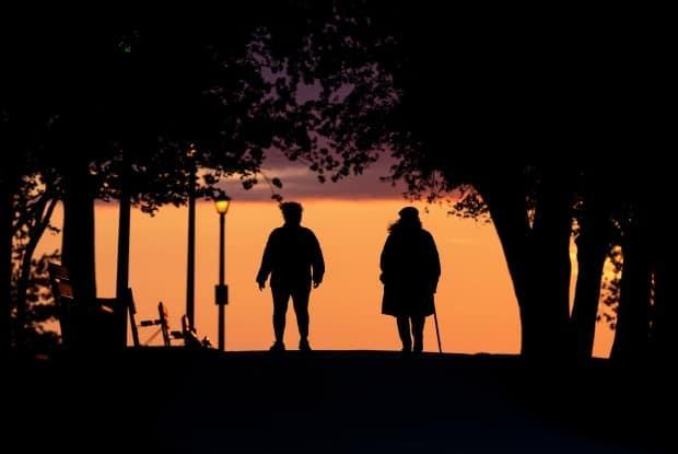 People walk as the sun sets at Britannia Park in Ottawa on Friday, July 30, 2021.  (Justin Tang/The Canadian Press - image credit)