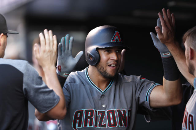 Arizona Diamondbacks' David Peralta is congratulated as he returns to the dugout after hitting a solo home run off Colorado Rockies starting pitcher German Marquez during the third inning of a baseball game Friday, June 8, 2018, in Denver. (AP Photo/David Zalubowski)
