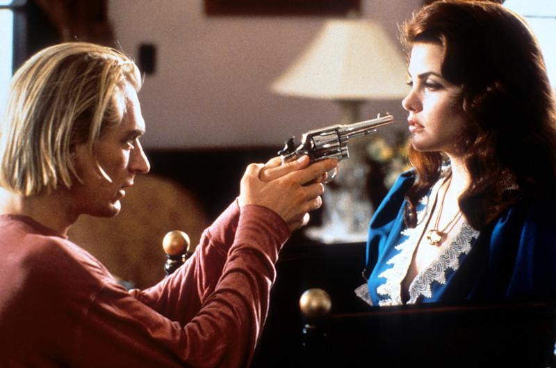 Julian Sands holding a gun Sherilyn Fenn's face in a scene from the film 'Boxing Helena', 1993. (Photo by Mainline Pictures/Getty Images)
