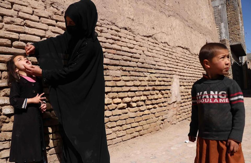 A polio worker administers the vaccine to Afghan children in Herat, Afghanistan, 31 March