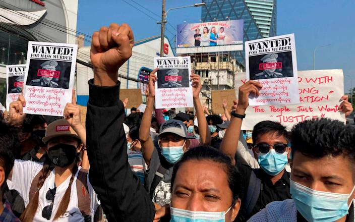 Protesters hold up Wanted posters with an image of Myanmar's Commander-in-Chief Senior Gen. Min Aung Hlaing, as they march in Yangon - AP
