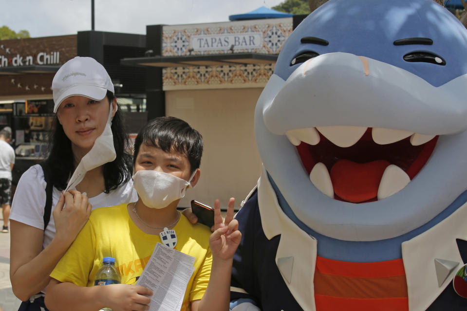 A woman takes off her face mask for a photograph at the Ocean Park amusement park in Hong Kong, Saturday, June 13, 2020. Hong Kong's Ocean Park reopened Saturday after nearly four months of closure due to the coronavirus pandemic. The animal and nature-themed attraction combines pandas, penguins, roller coasters and other rides, and has been a Hong Kong icon since its opening in 1977. (AP Photo/Kin Cheung)