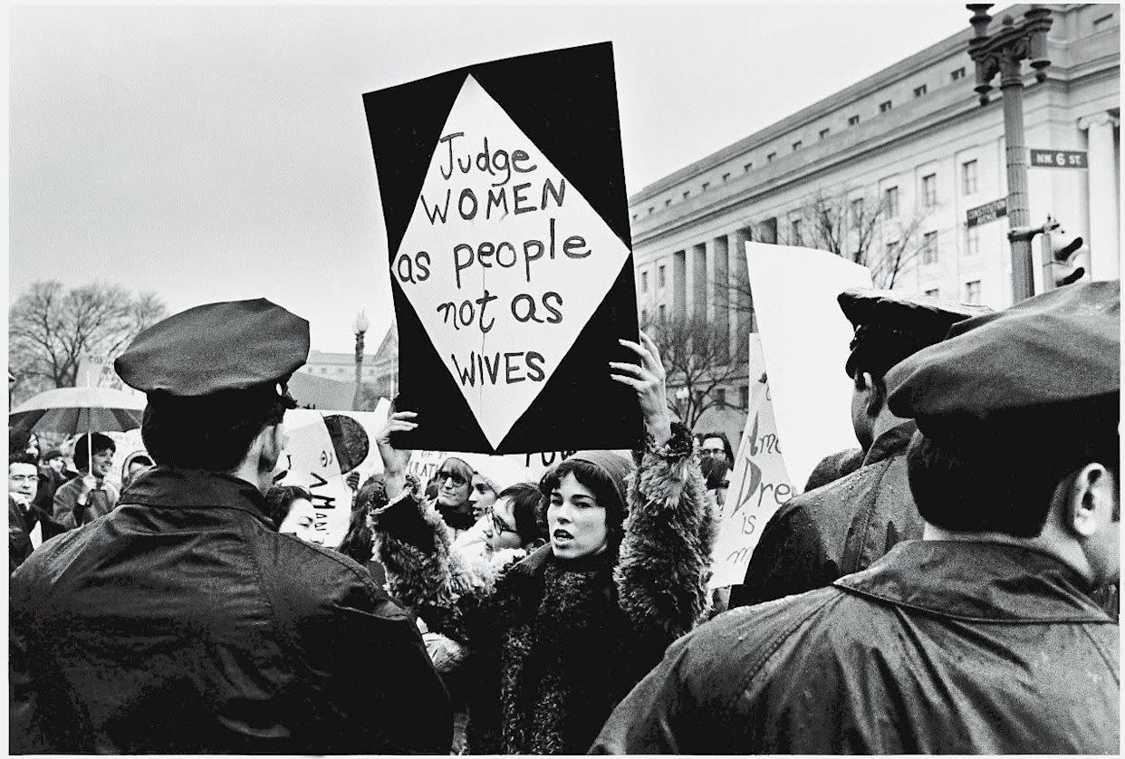 A young American woman holds up a sign as she protests for women's rights in front of the Federal Trade Commission headquarters while policemen look on during Richard Nixon's inauguration weekend, Washington, DC, January 18-21, 1969. Her sign reads 'Judge women as people not as wives.'