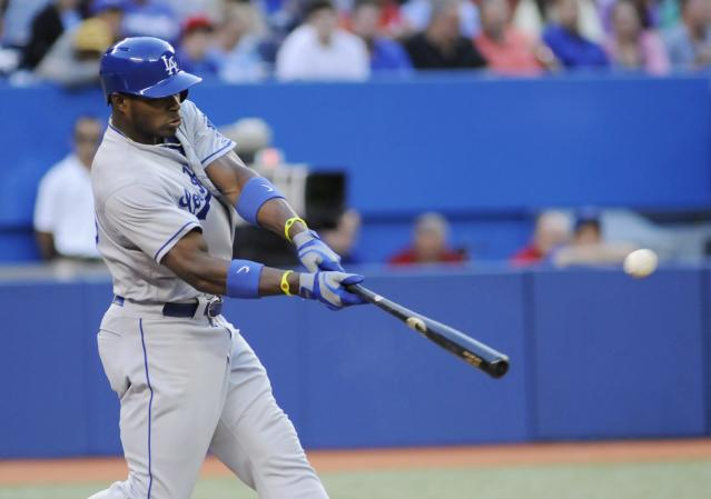 Los Angeles Dodgers' Yasiel Puig hits a double to score teammate Carl Crawford during the third inning of a baseball game on Wednesday July 24, 2013, in Toronto. (AP Photo/The Canadian Press, Jon Blacker)