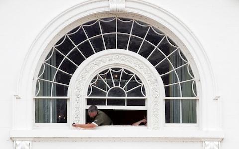 A worker hangs out of a window of the White House during renovation work at the White House in Washington, DC, USA, 11 August 2017 - Credit: EPA
