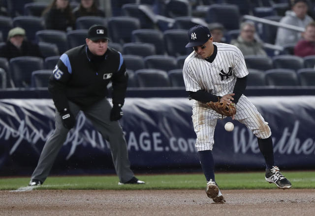 New York Yankees third baseman Ronald Torreyes can't contain a bad hop on a ball hit by Toronto Blue Jays' Yangervis Solarte during the fourth inning of a baseball game Thursday, April 19, 2018, in New York. Solarte was safe at first on Torreyes' bad throw to the bag. (AP Photo/Julie Jacobson)