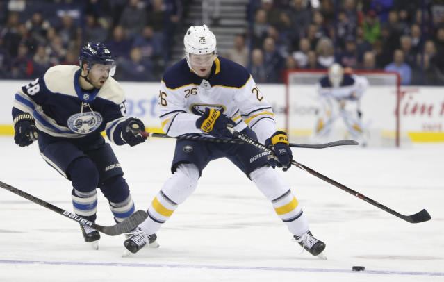 Buffalo Sabres' Rasmus Dahlin, right, of Sweden, carries the puck across the blue line as Columbus Blue Jackets' Oliver Bjorkstrand, of Denmark, defends during the first period of an NHL hockey game Tuesday, Jan. 29, 2019, in Columbus, Ohio. (AP Photo/Jay LaPrete)