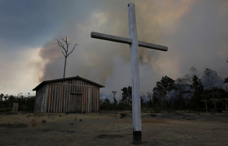 Catholic church is pictured as fire burns tract of Amazon jungle being cleared by loggers and farmers near Porto Velho