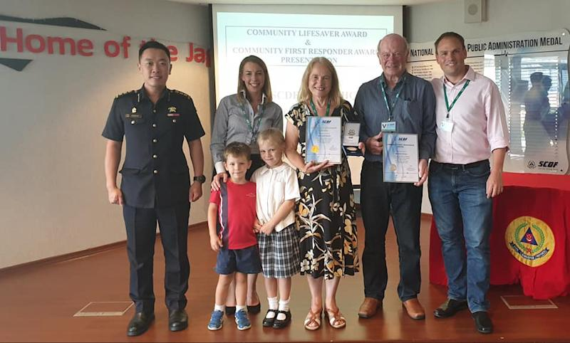 The Brewins (posing with their awards) pictured with members of their family who are residing in Singapore, on 11 October, 2019. (PHOTO: SCDF/Facebook)