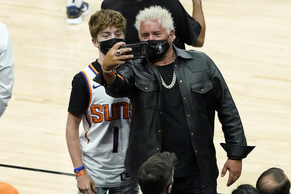 Television personality Guy Fieri, right, takes a selfie with his son, Hunter Fieri, prior to Game 1 of an NBA basketball second-round playoff series between the Phoenix Suns and the Denver Nuggets, Monday, June 7, 2021, in Phoenix. (AP Photo/Matt York)