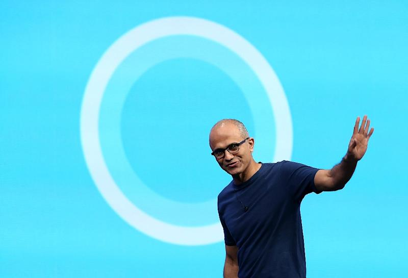 Microsoft CEO Satya Nadella walks in front of the new Cortana logo during the 2014 Microsoft Build developer conference on April 2, 2014 in San Francisco
