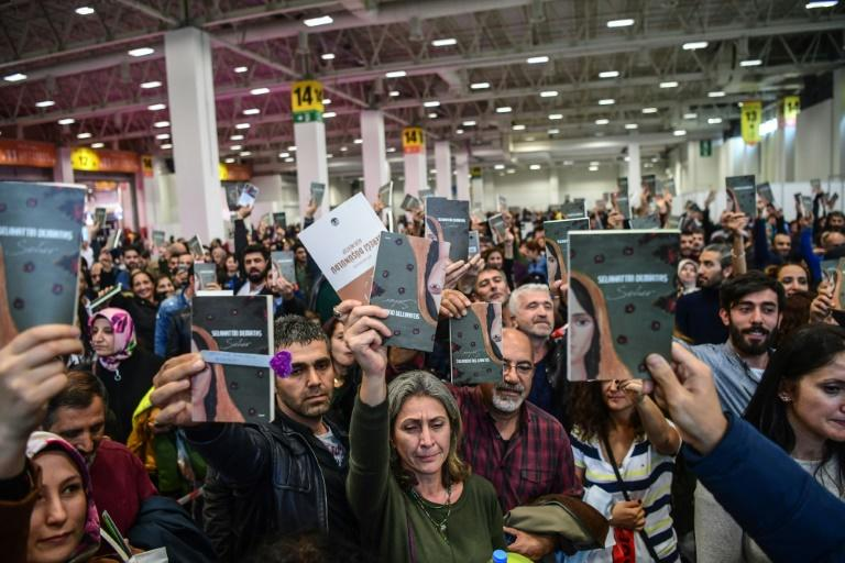 Demirtas supporters hold up the book of short stories he wrote in prison