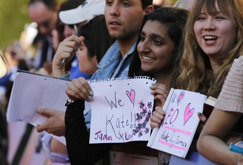 Fans holding paper saying 'We love Kate, James & Leo' at the 'Titanic 3D' UK film premiere at the Royal Albert Hall in Kensington, West London, Tuesday, March 27, 2012. The re-launch of the Titanic 3D version comes 15 years after the film was a huge box office hit. (AP Photo/Joel Ryan)