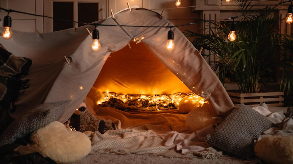handmade tent with blankets, pillows, toys and lights in room.