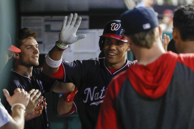 Washington Nationals' Juan Soto celebrates his solo home run with his teammates during the fourth inning of their baseball game against the Cincinnati Reds at Nationals Park, Tuesday, Aug. 13, 2019, in Washington. (AP Photo/Alex Brandon)