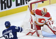Calgary Flames goaltender David Rittich (33) gets a piece of a shot by Toronto Maple Leafs left wing Alexander Barabanov (94) during third period NHL hockey action in Toronto on Monday, Feb. 22, 2021. (Nathan Denette/The Canadian Press via AP)