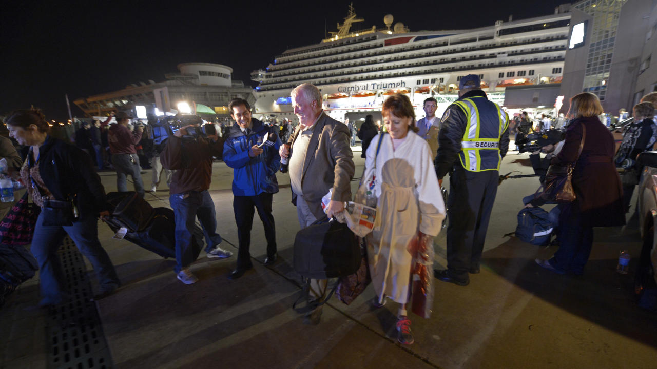 Passengers from the cruise ship Carnival Triumph are questioned by reporters after they disembarked in Mobile, Ala., Thursday, Feb. 14, 2013. The ship with more than 4,200 passengers and crew members has been idled for nearly a week in the Gulf of Mexico following an engine room fire. (AP Photo/John David Mercer)