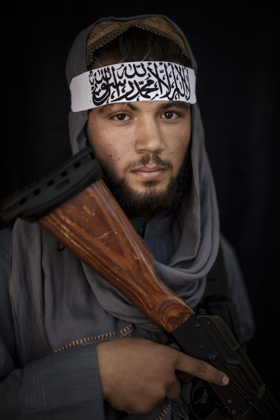 Taliban fighter Osman, 20, poses for a photo at a police station holding his AK-47 rifle and a wearing a new Taliban-flag headband on top of his scarf, in Kabul, Afghanistan, Thursday, Sept. 16, 2021. (AP Photo/Felipe Dana)