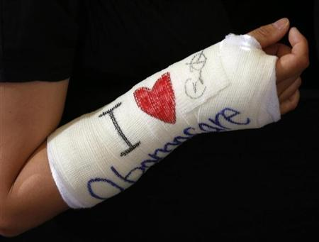 Cathey Park shows her cast signed by U.S. President Obama after he spoke about health insurance at Faneuil Hall in Boston