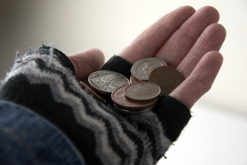 Collection of British coins in gloved hand