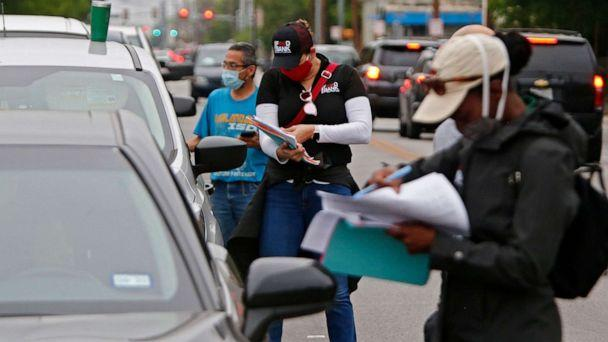 PHOTO: People waiting in line to get food at the San Antonio Food Bank distribution center being held in the parking lot at the Alamo Dome in San Antonio, April 17, 2020, are checked.  (Larry W Smith /EPA via Shutterstock)