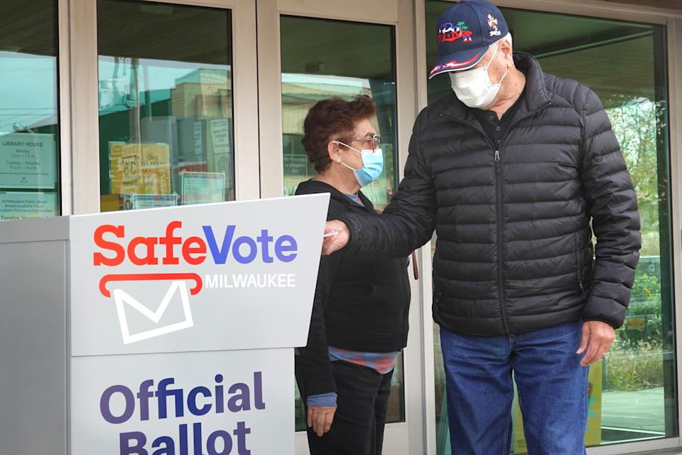 Residents drop mail-in ballots in an official ballot box outside of the Tippecanoe branch library on October 20, 2020 in Milwaukee, Wisconsin. (Scott Olson/Getty Images)