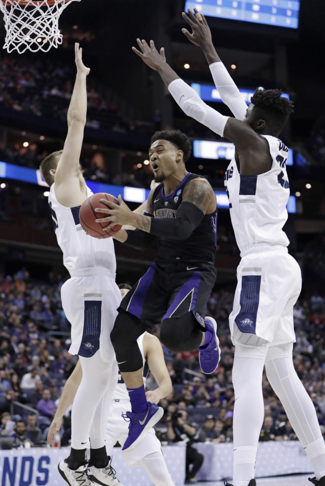 Washington's David Crisp, center, drives to the basket between Utah State's Quinn Taylor, left, and Neemias Queta in the first half during a first round men's college basketball game in the NCAA Tournament in Columbus, Ohio, Friday, March 22, 2019. (AP Photo/Tony Dejak)