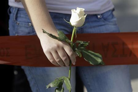 A woman holds a white rose as she stands near the local offices of far-right Golden Dawn party, following last night's shooting, in a northern suburb of Athens