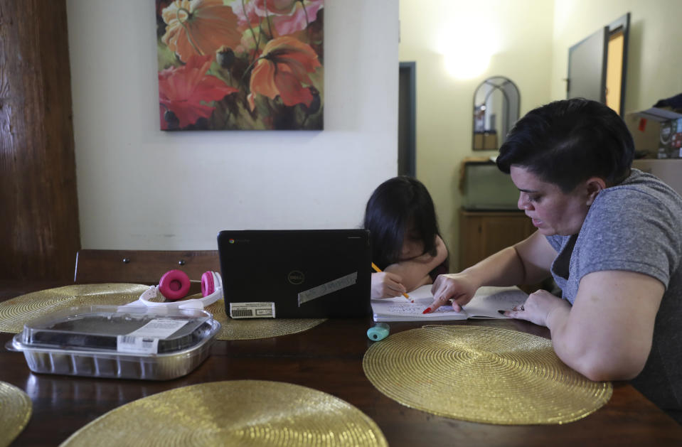 Chicago parent Rosa Esquivel, right, helps her 10-year-old daughter Veronica Esquivel, who attends Andrew Jackson Elementary School, with her homework after virtual school hours, Wednesday, Feb. 10, 2021, at their residence in Chicago's predominantly Hispanic Pilsen neighborhood. Rosa is not sending her children to school and doesn't believe that the schools will be safe from the coronavirus, which made her mother and sister sick and killed an aunt and uncle in her native Guatemala. (AP Photo/Shafkat Anowar)